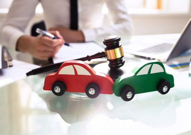 Gavel on table next to 2 toy cars